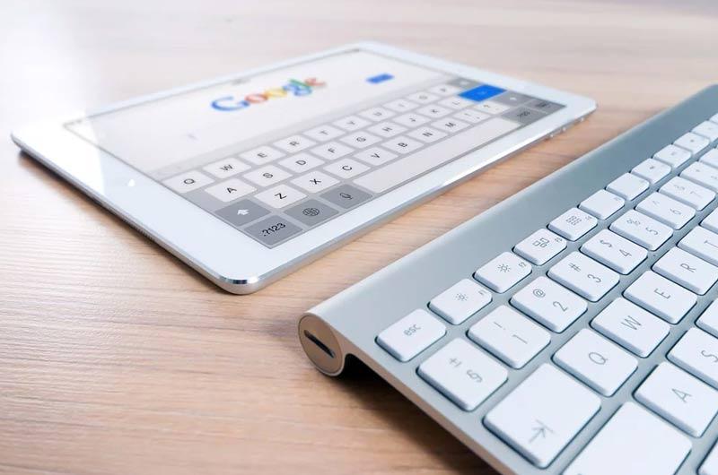 tablet sobre mesa de madera navegando por google al lado de un teclado