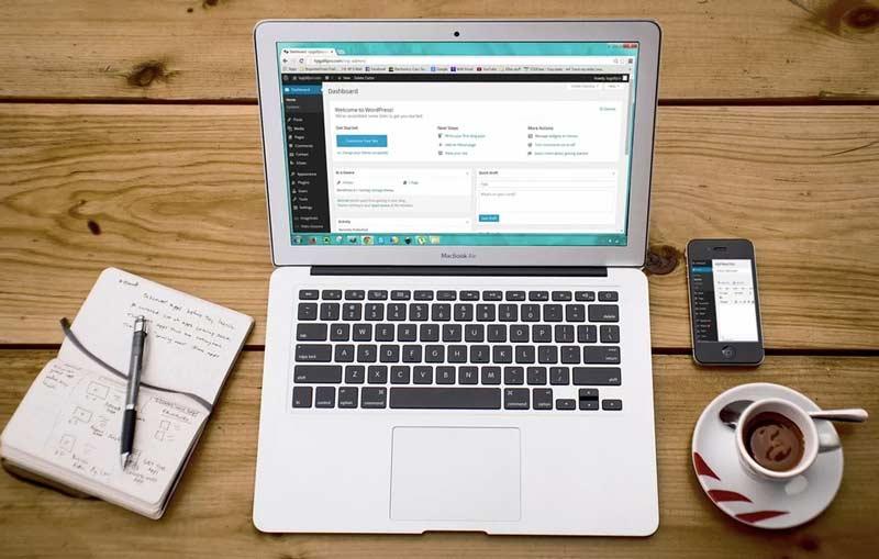 ordenador portátil sobre mesa de madera en el que se muestra el dashboard de un cms