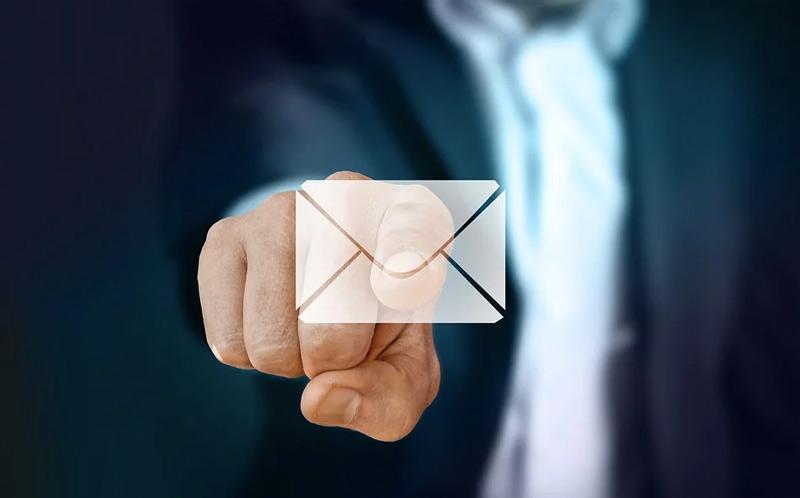mano aputando a un sobre que simboliza un email