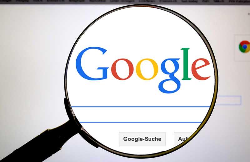 lupa sobre pantalla de ordenador mostrando la palabra google