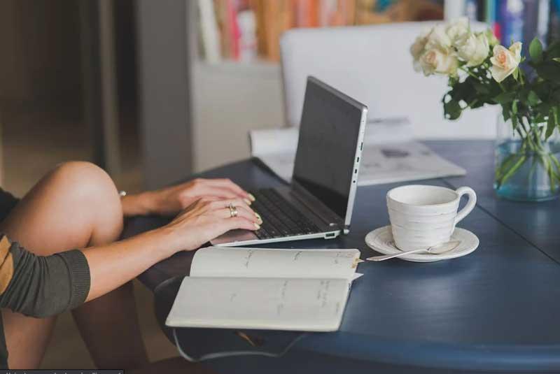 persona sentada con el ordenador apoyado en la mesa escribiendo en el teclado