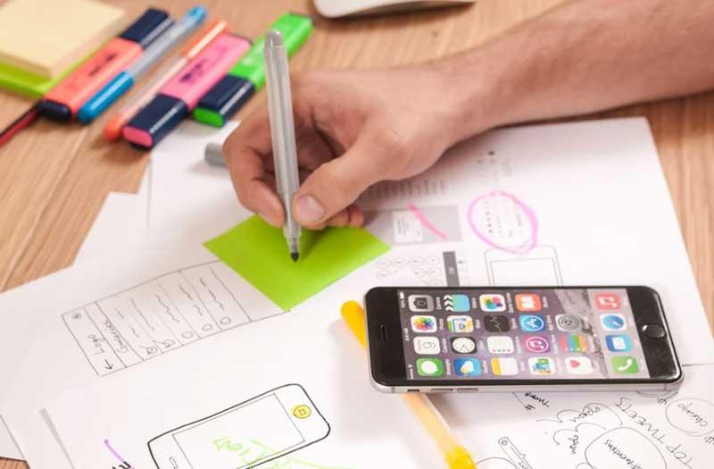 papeles sobre la mesa en la que se muestra el diseño de una app de móvil